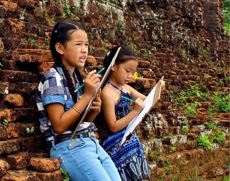 Học sinh Duy Xuyên vẽ tranh tại Khu đền tháp Mỹ Sơn. Ảnh: PHƯƠNG THẢO