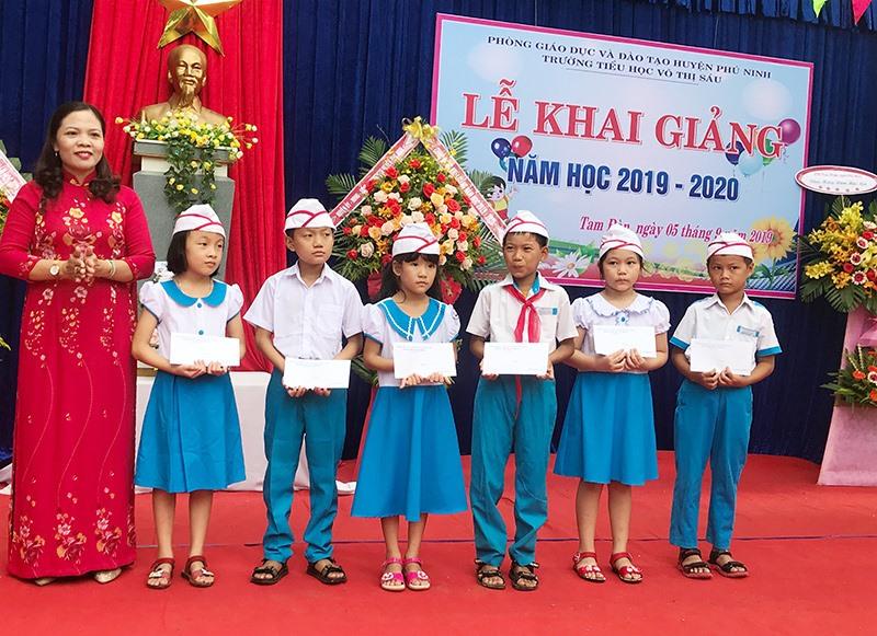 Lãnh đạo Phòng GD-ĐT huyện Phú Ninh trao quà cho học sinh vượt khó Trường Tiểu học Võ Thị Sáu. Ảnh: C.N