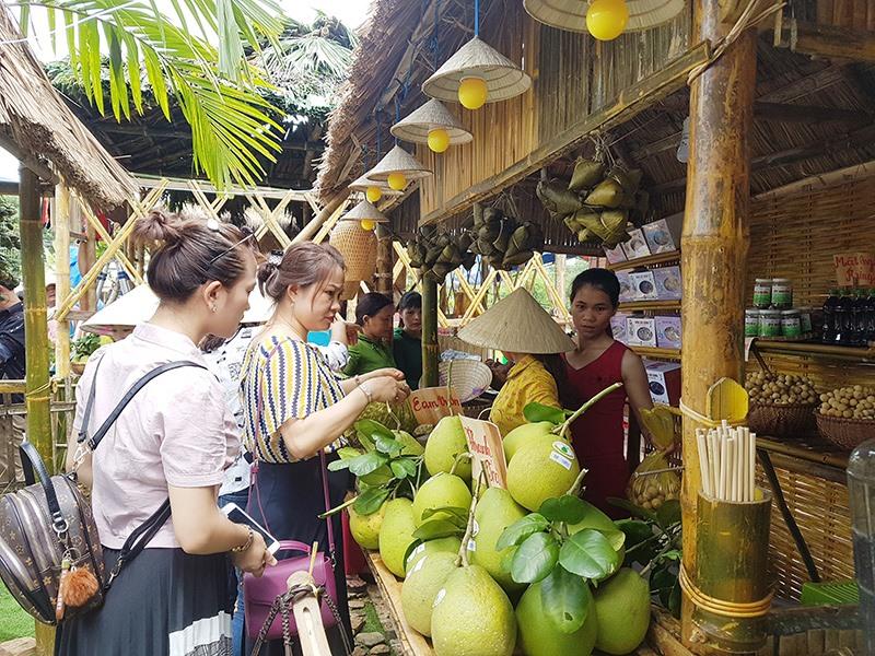 Du khách đến tham quan, mua sắm nông sản tại hội làng. Ảnh: D.L