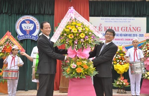 Thay mặt lãnh đạo tỉnh, Trưởng ban Nội chính Tỉnh ủy Nguyễn Ngọc Truyền (bìa trái) tặng hoa chúc mừng Trường THCS Nguyễn Du. Ảnh: N.Đ