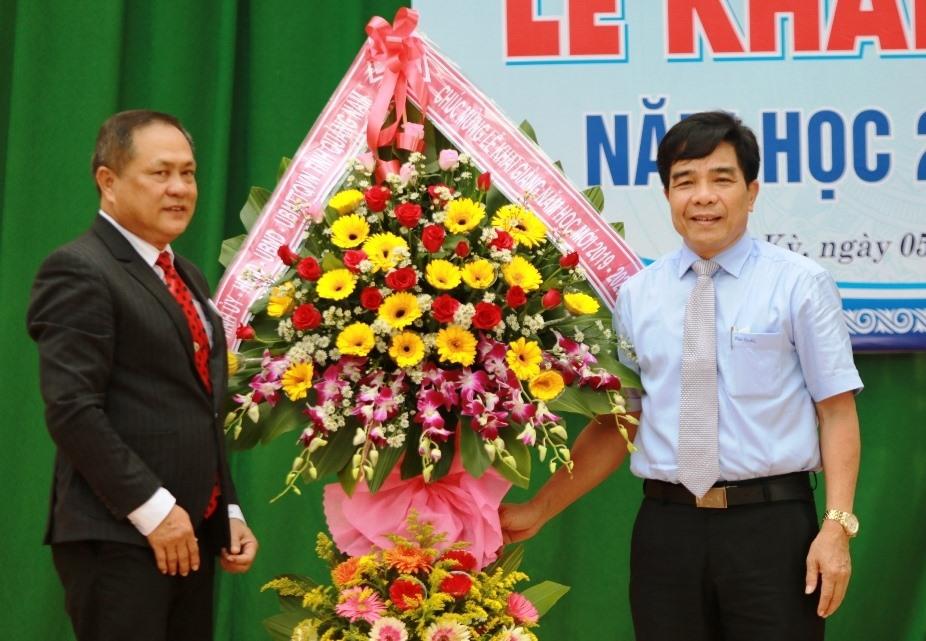 Phó Bí thư Thường trực Tỉnh ủy Lê Văn Dũng (bìa phải) tặng lẵng hoa chúc mừng thầy và trò Trường THPT Trần Cao Vân. Ảnh: T.C
