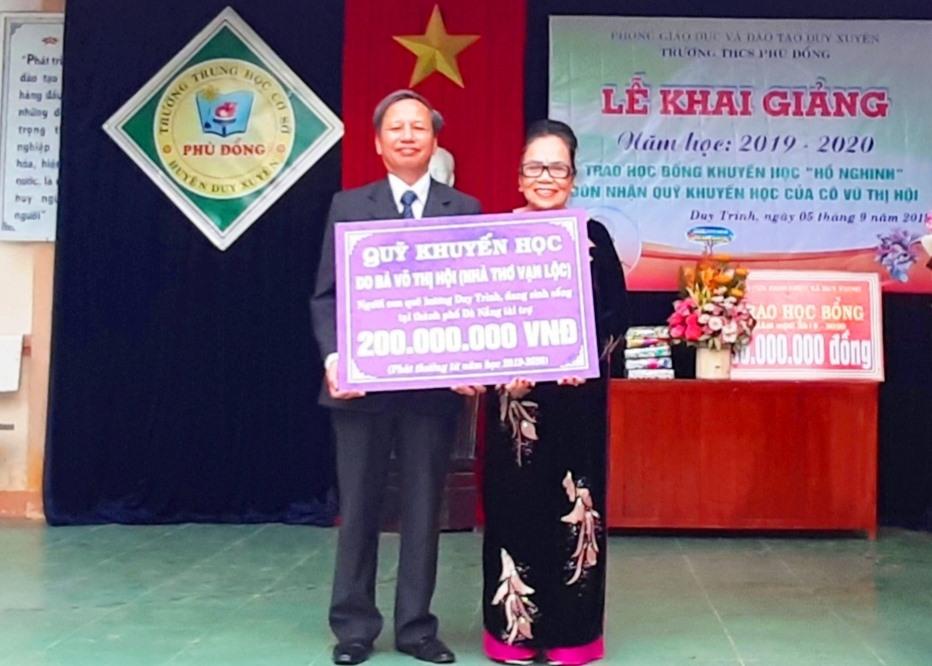 Bà Võ Thị Hội trao 200 triệu đồng cho đại diện Trường THCS Phù Đổng. Ảnh: HOÀI NHI