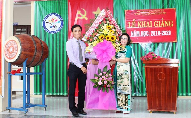 Lãnh đạo huyện Phú Ninh tặng hoa chúc mừng Trường THCS Lê Quý Đôn nhân lễ khai giảng năm học mới. Ảnh: H.C