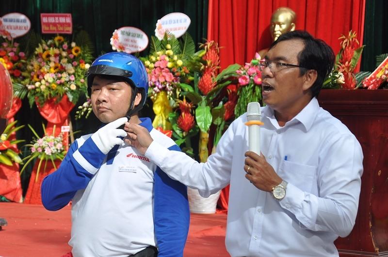 Đại diện Ban An toàn giao thông tỉnh cùng nhân viên Công ty Honda Việt Nam hướng dẫn cách đội MBH cho học sinh. Ảnh: V.ANH