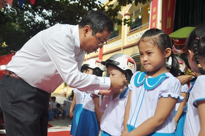 Ông Lê Văn Sinh tặng MBH cho học sinh Trường Tiểu học Trần Quốc Toản. Ảnh: V.ANH