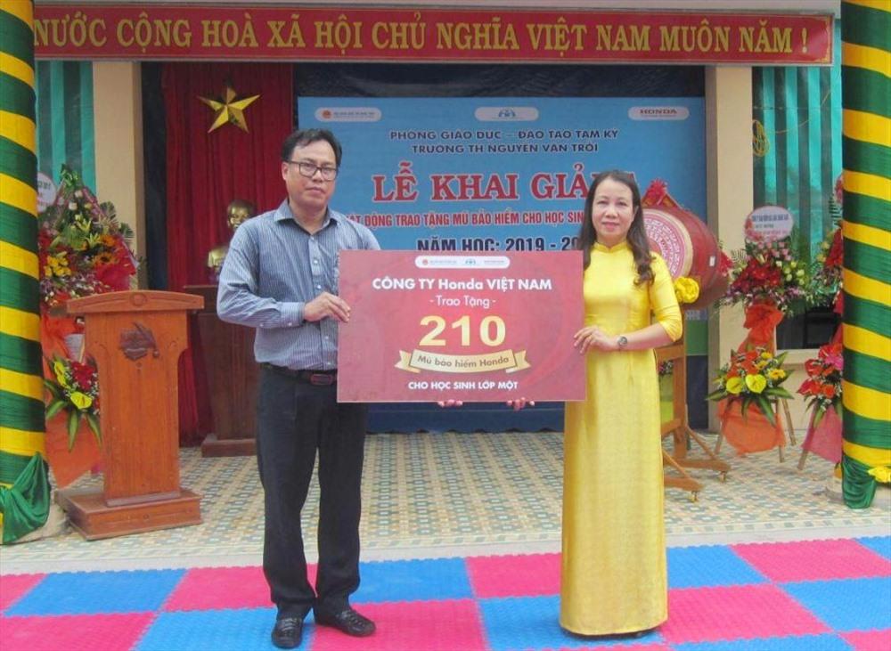 Lãnh đạo Trường Tiểu học Nguyễn Văn Trỗi (phải) nhận bảng tượng trưng trao tặng 210 MBH từ Công ty Honda Quốc Tiến 2 Tam Kỳ. Ảnh: C.N