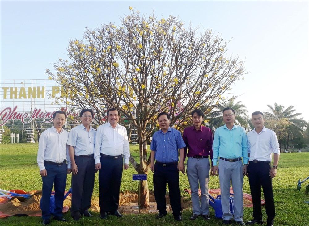 Lãnh đạo tỉnh và thành phố chụp hình lưu niệm bên cây mai.