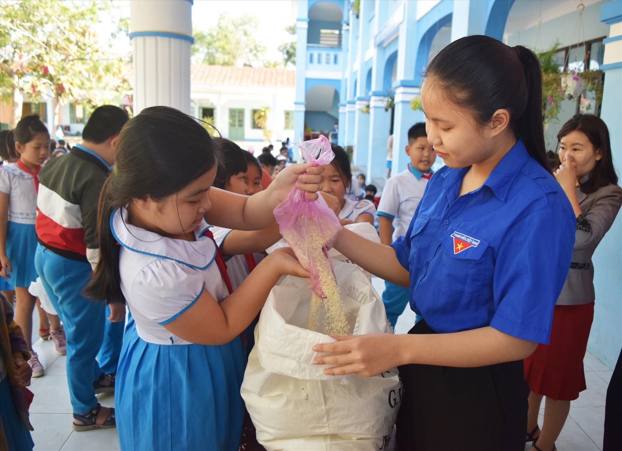 Học sinh ủng hộ gạo cho chương trình hủ gạo tình thương do đoàn xã Tam Nghĩa phát động - Ảnh: THÁI CƯỜNG
