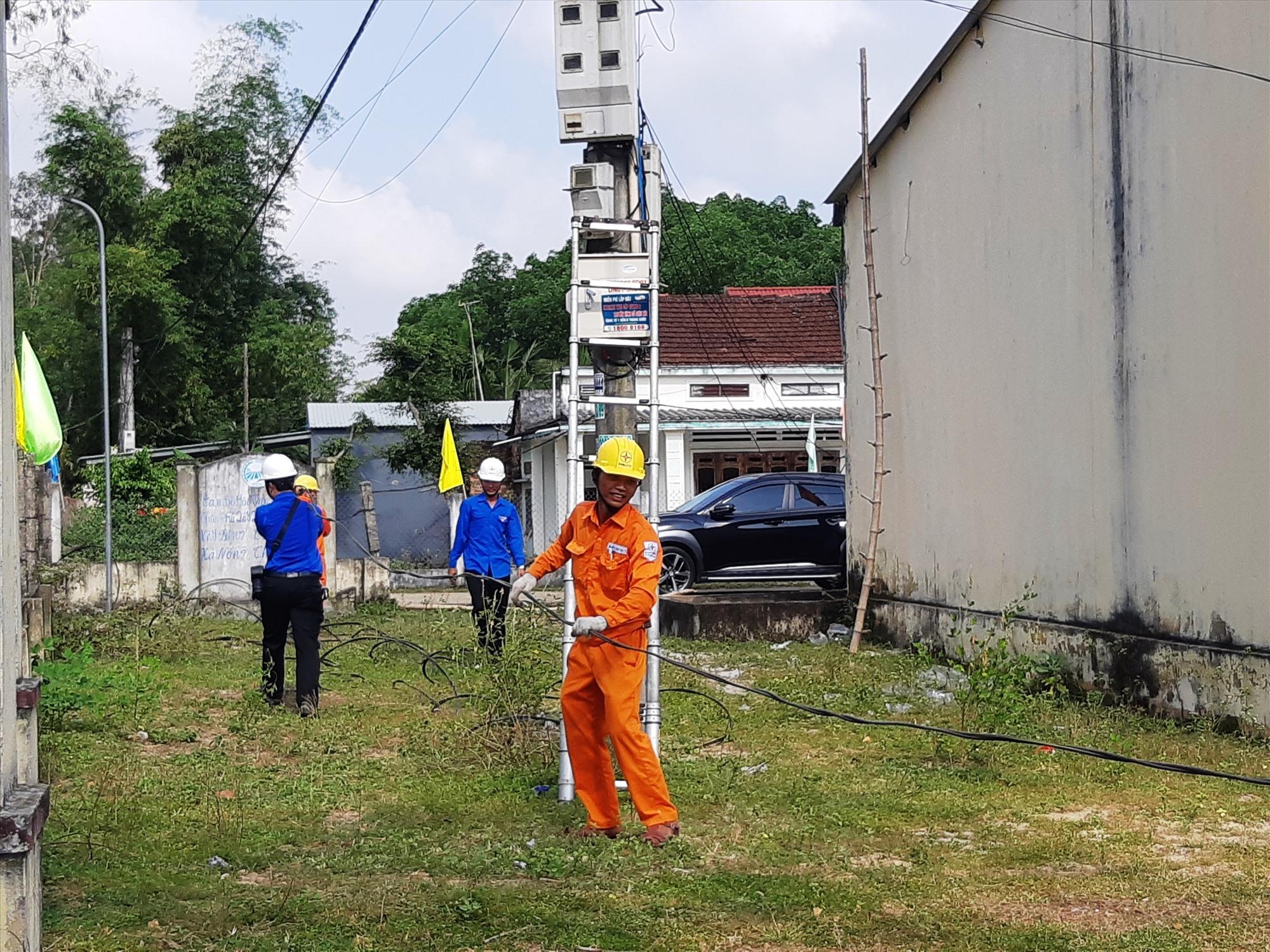 Kéo đường dây điện tạo hệ thống điện thắp sáng đường quê tại xã Tam Phú, Tam Kỳ. Ảnh: HOÀNG LIÊN