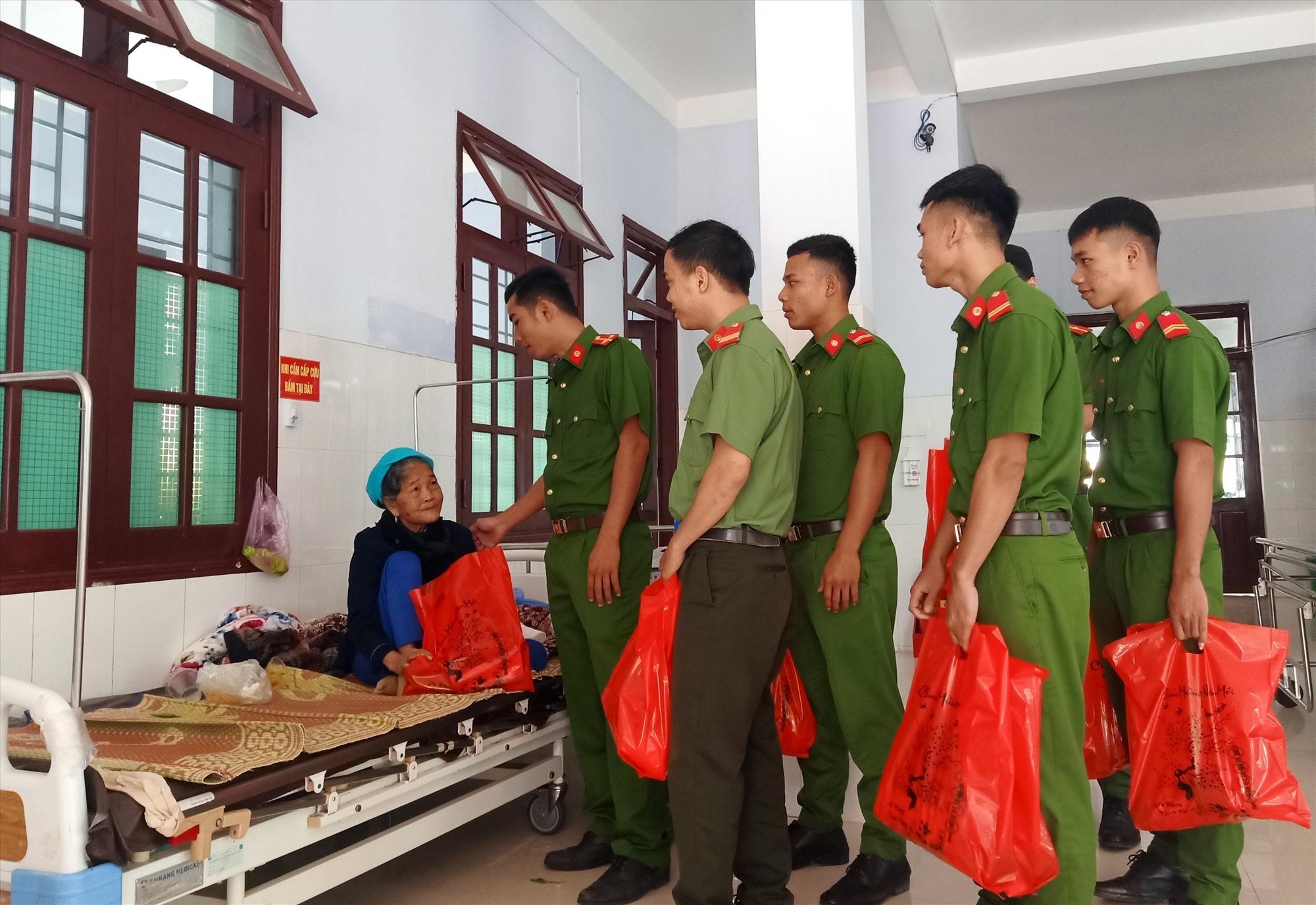 Cán bộ, chiến sĩ Công an huyện Đông Giang động viên, trao quà tết cho bệnh nhân. Ảnh: Đ.N
