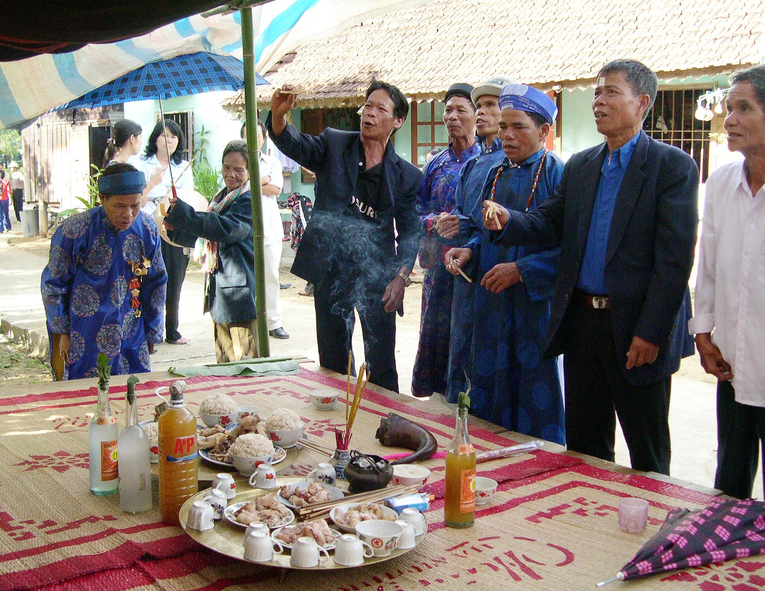 Những người già Cơ Tu thực hiện nghi thức ném bông lúa trong đám cưới. Ảnh: P.V.B