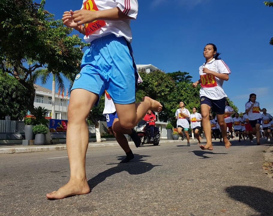 Những đôi chân trần của các nữ vận động viên miền núi trên đường chạy 1.500m nữ THPT.