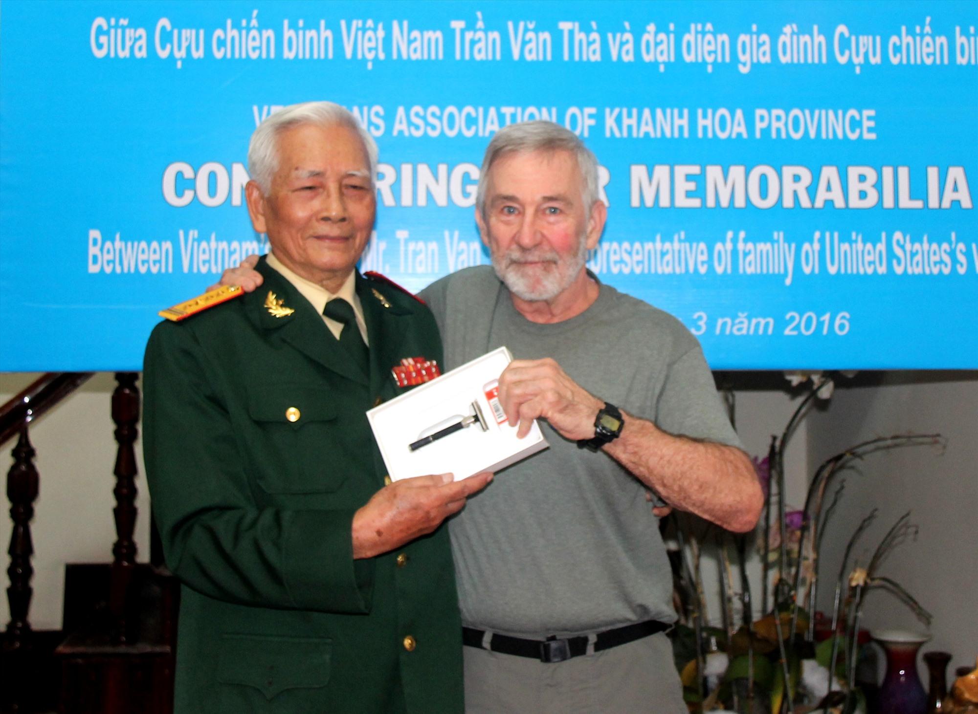 Đại tá Trần Văn Thà trao lại kỷ vật cho một cựu binh Mỹ.