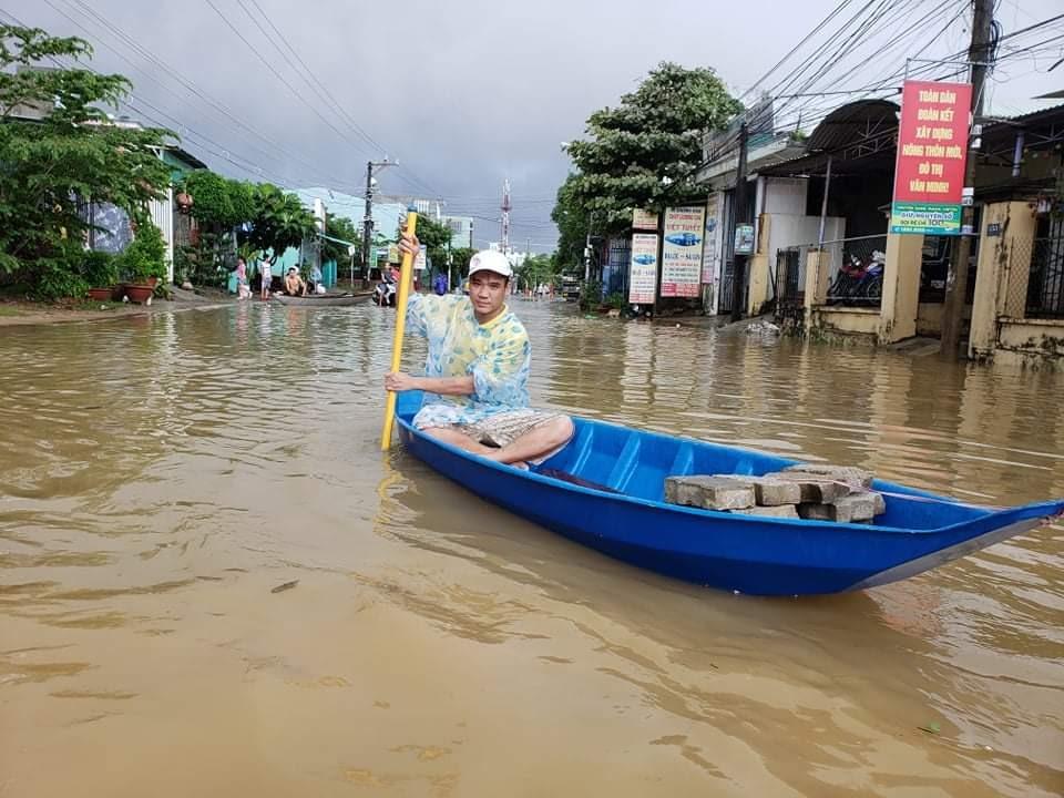 Một người dân đang chèo ghe trên nước lũ tại khối Nghĩa Nam, thị trấn Ái Nghĩa, Đại Lộc, lúc 10h sáng nay. Ảnh: THANH THẮNG