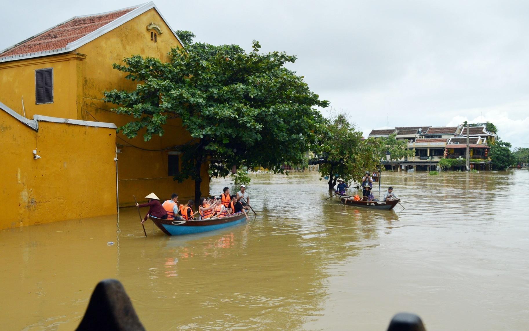 Du khách khám phá Chùa Cầu mùa lụt từ xa bằng thuyền.