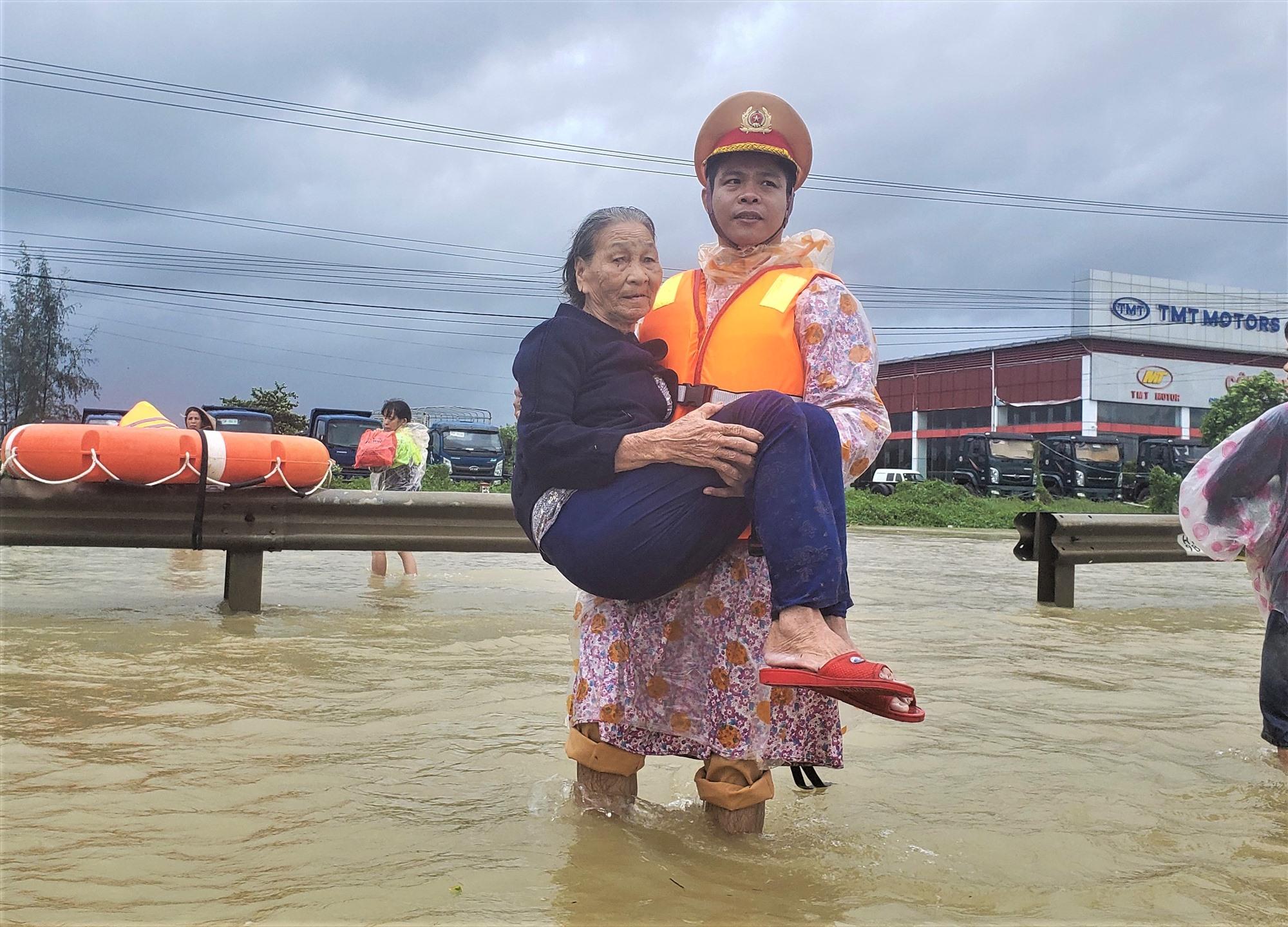 Cán bộ Phòng Cảnh sát đường thủy Công an tỉnh Quảng Nam bồng cụ già qua khỏi dòng nước lũ. Ảnh: L.T