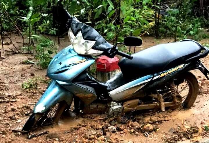 Một chiếc xe máy dựng ven đường bị sạt lở đất vùi bánh. Ảnh: Đ.N
