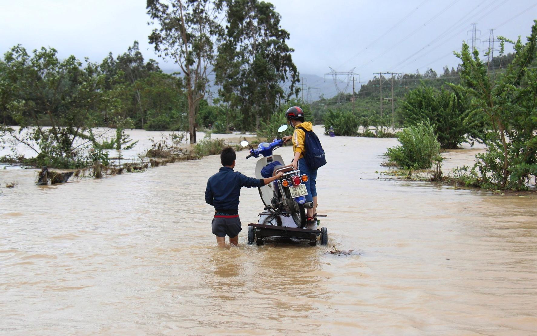 Dùng xe bò vận chuyển xe máy qua dòng nước lũ. Ảnh:H.A