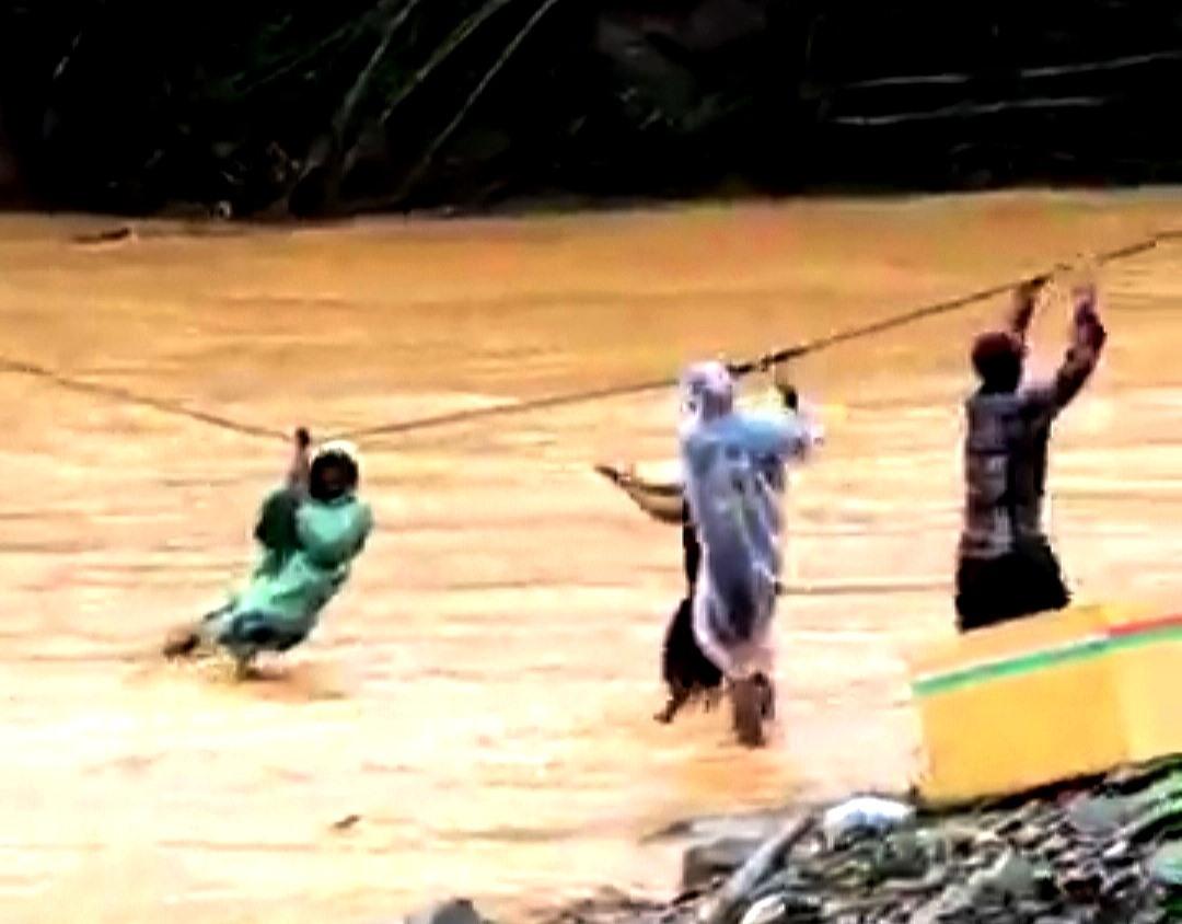 Bất chấp nguy hiểm, người dân đu mình trên dây giữa dòng nước lũ chảy xiết. Ảnh cắt từ clip
