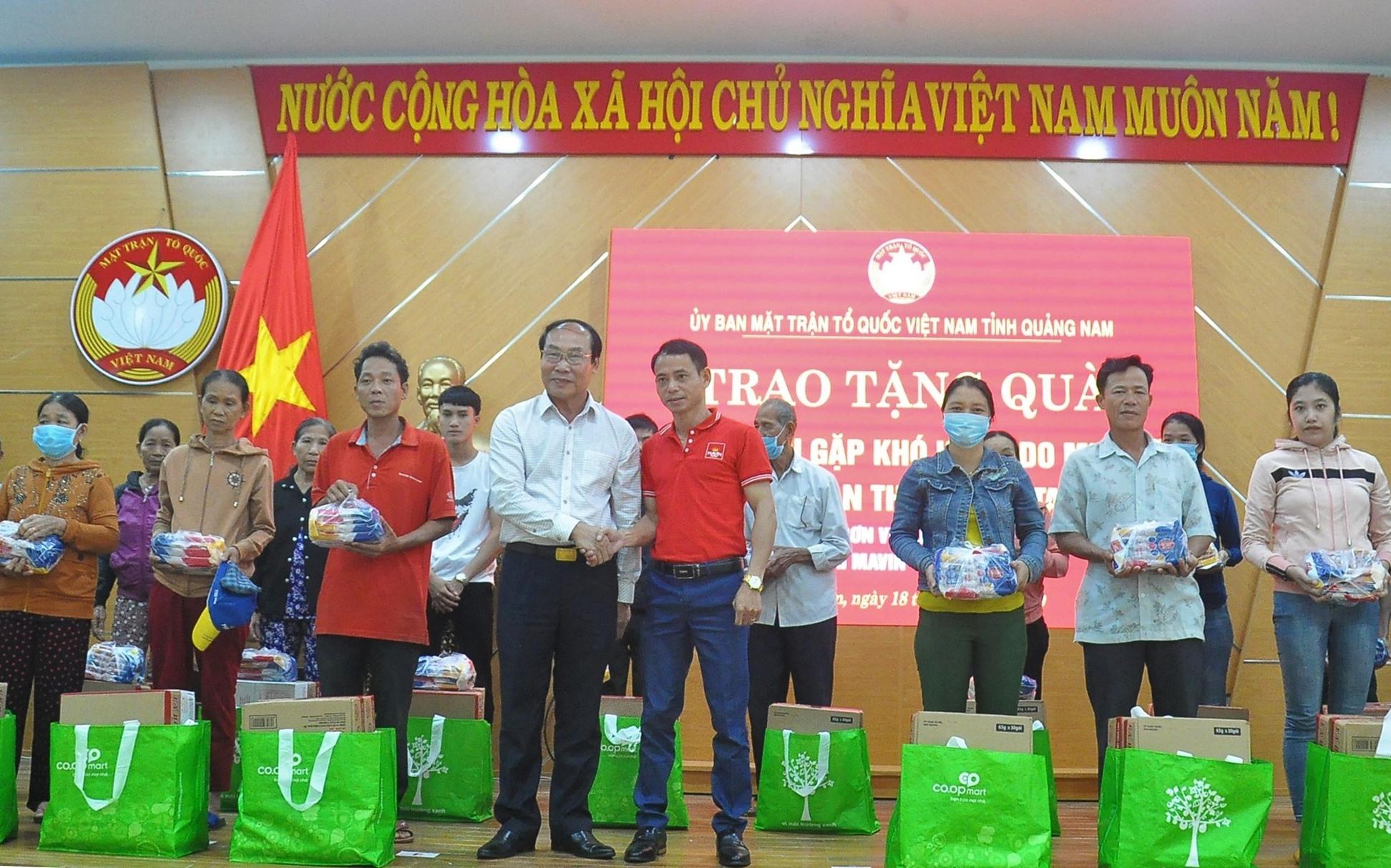 Chủ tịch Ủy ban MTTQ Việt Nam tỉnh Võ Xuân Ca cùng nhà tài trợ trao quà cho người dân vùng lũ Tam Kỳ. Ảnh: VINH ANH