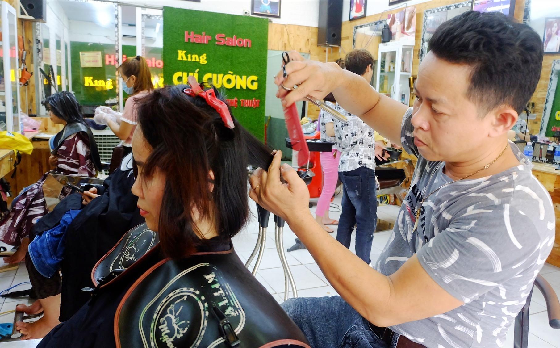 Anh Ung Nho Cường đang tạo mẫu tóc cho khách hàng. Ảnh: A.B