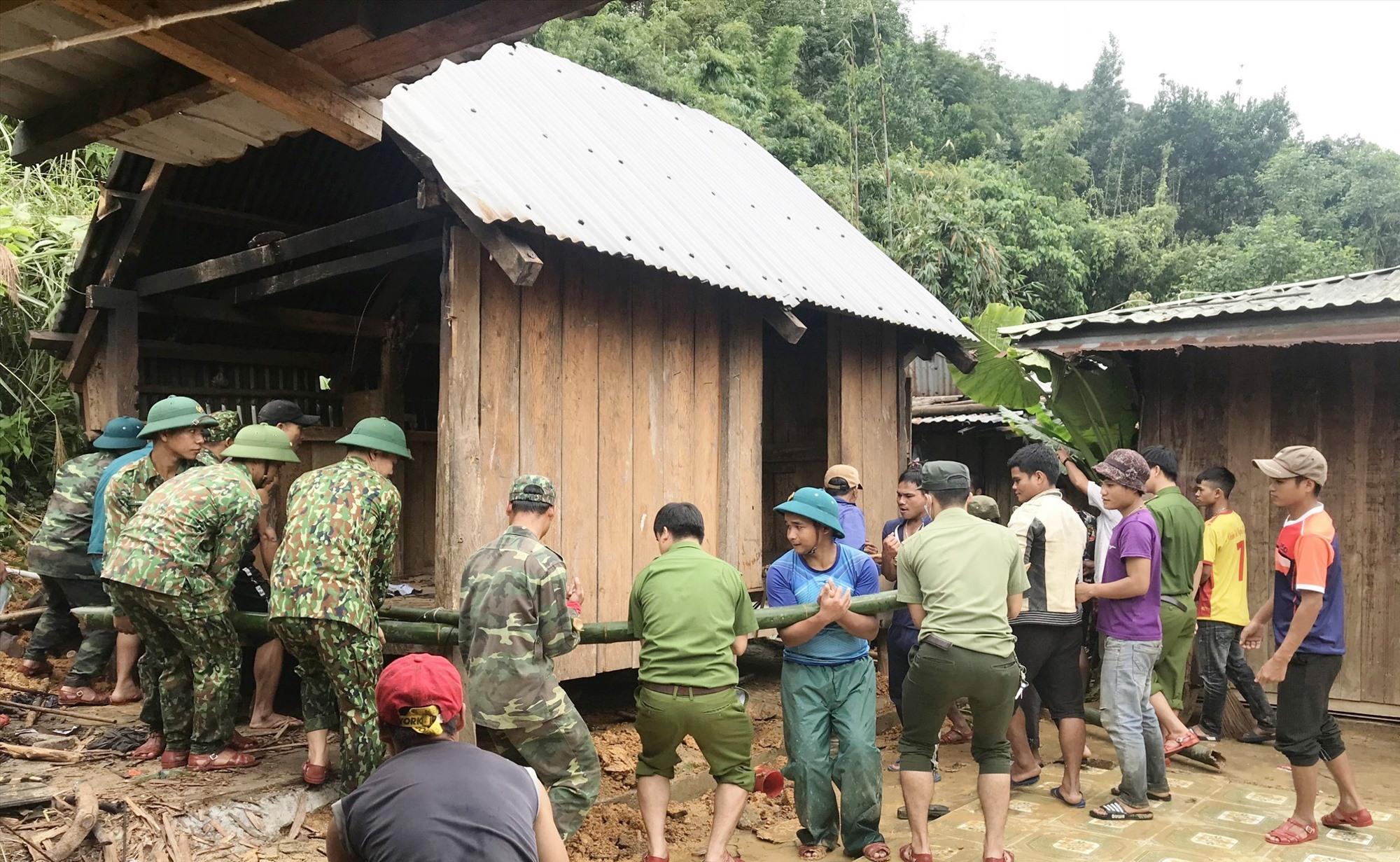 Cán bộ, chiến sĩ Đồn Biên phòng A Nông giúp dân di chuyển nhà do sạt lở tại thôn Pơning, xã Lăng, huyện Tây Giang. Ảnh: VĂN VINH