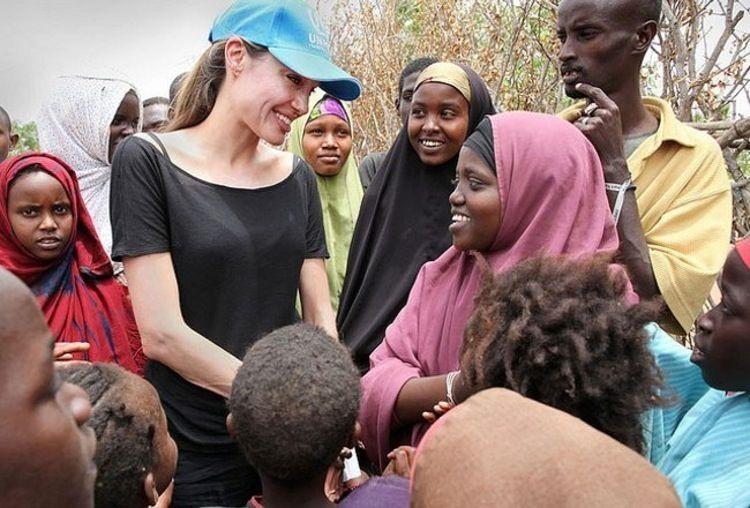 Angelina Jolie (đội mũ) trong một chuyến đi làm từ thiện. Ảnh: printerest