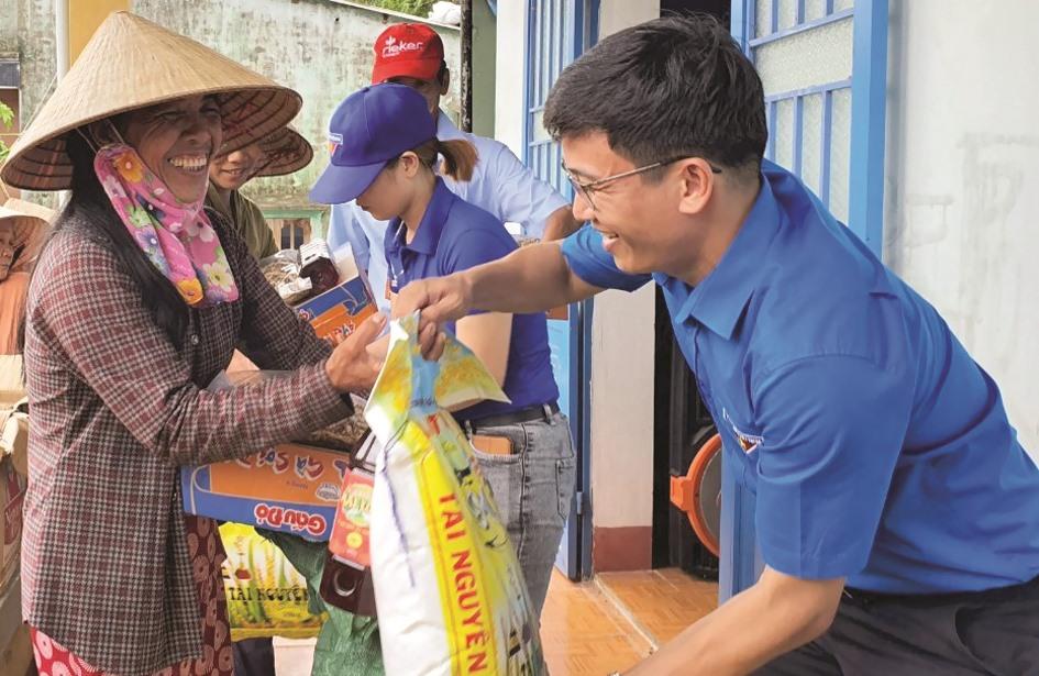 Người dân vùng lũ nhận quà hỗ trợ của tổ chức thanh niên, do anh Nguyễn Xuân Đức - Phó Bí thư Tỉnh đoàn, Chủ tịch Hội LHTN Việt Nam tỉnh trao tặng.