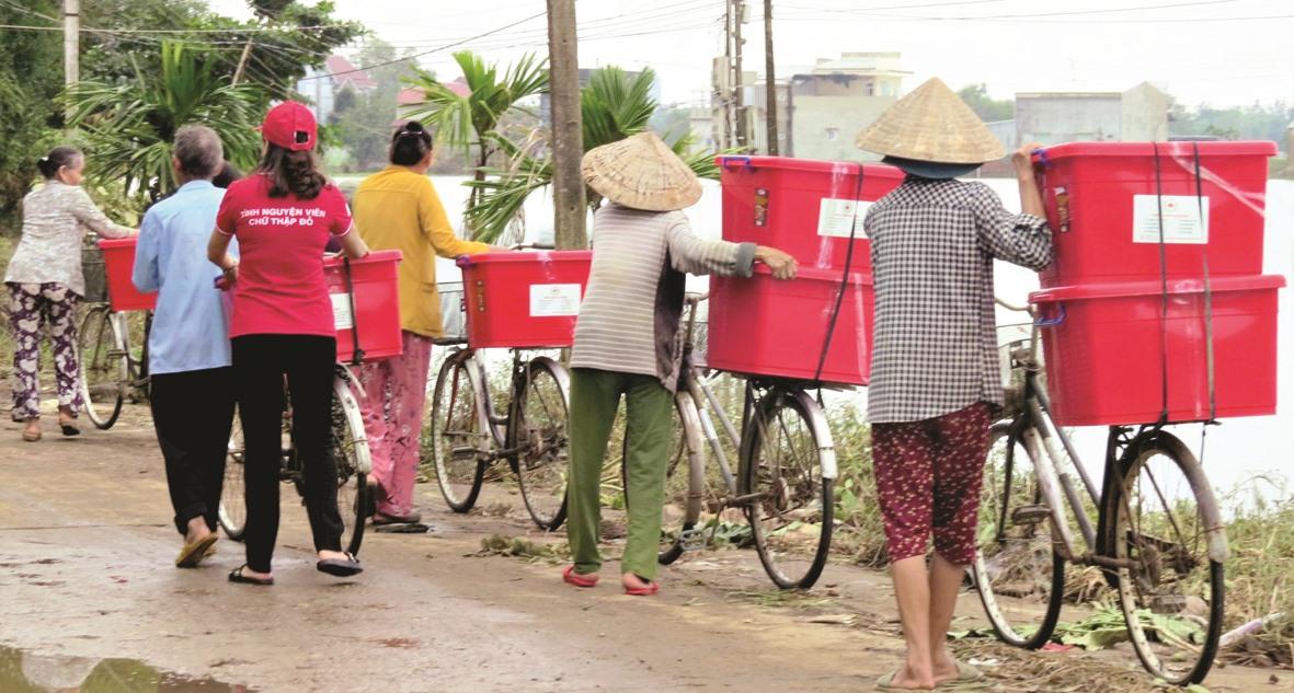 Người dân vùng lũ lụt nhận thùng hàng do Hội Chữ thập đỏ trao tặng. Ảnh: CTĐ