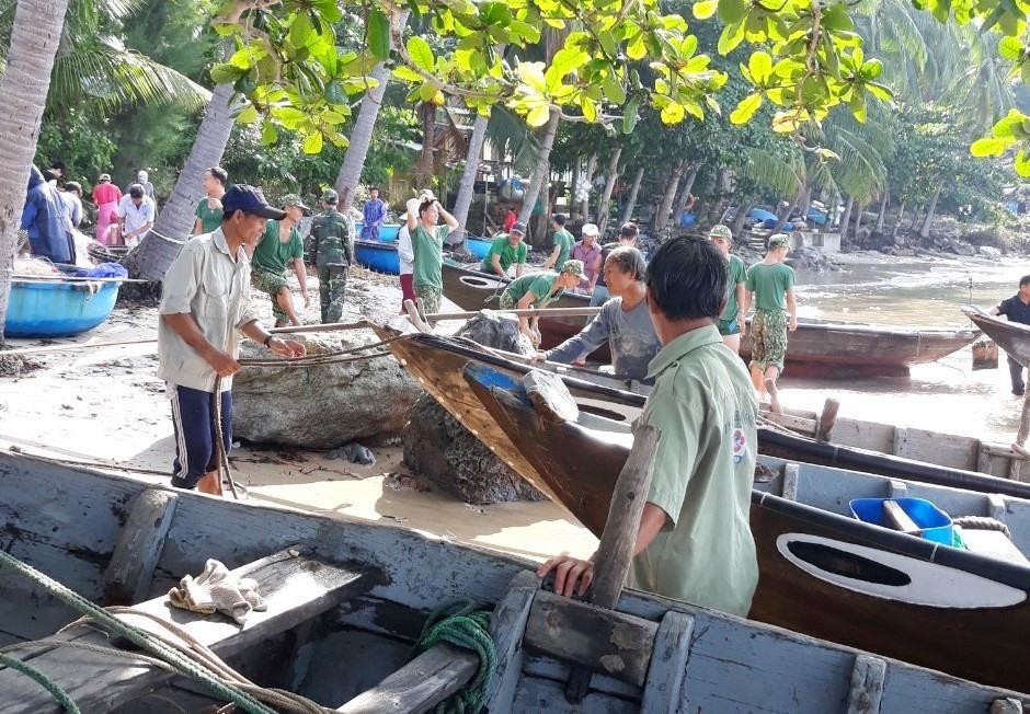 Lực lượng biên phòng giúp người dân đảo Cù Lao Chàm (xã Tân Hiệp) đưa những chiếc ghe lên bờ. Ảnh: BIÊN PHÒNG