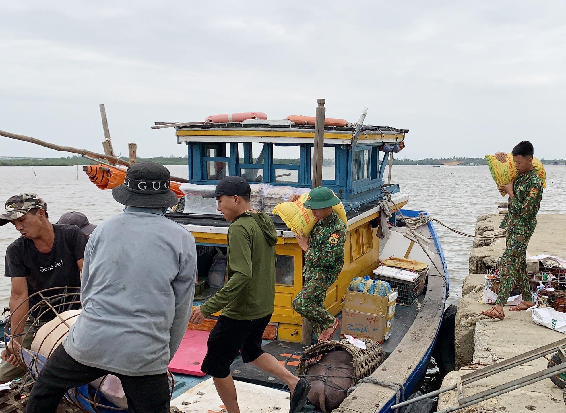 Giúp dân vận chuyển lương thực, thực phẩm ra đảo dự trữ trước bão số 9. Ảnh: T.C