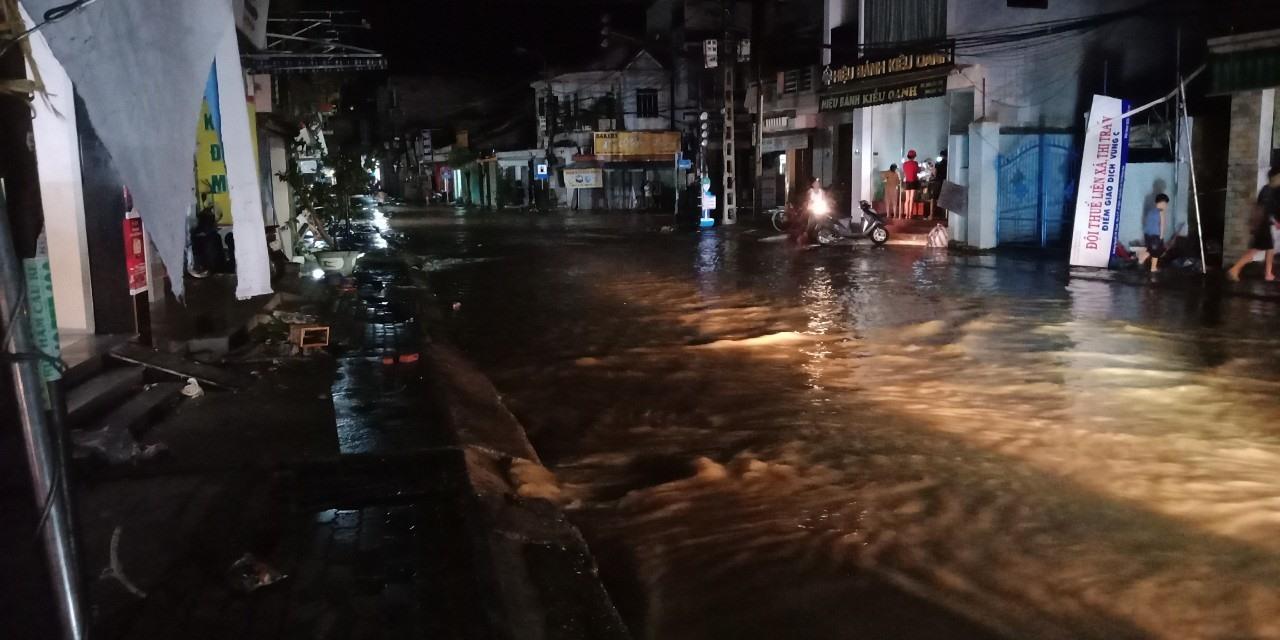 Nước lũ băng qua đường ở thị trấn Ái Nghĩa (Ảnh chụp lúc 8h30 phút tối 28.10). Ảnh: P. Đ.N