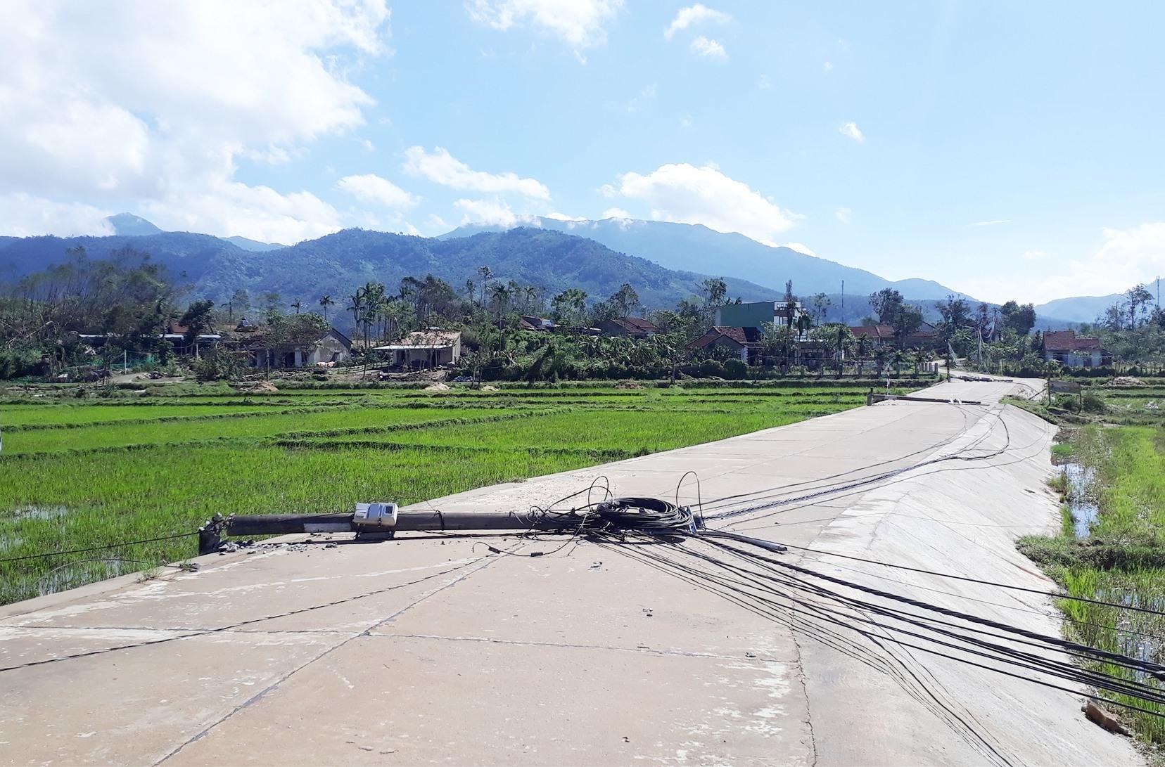 Nhiều trụ điện ngã đỗ ở Nông Sơn. Ảnh: Minh Thông