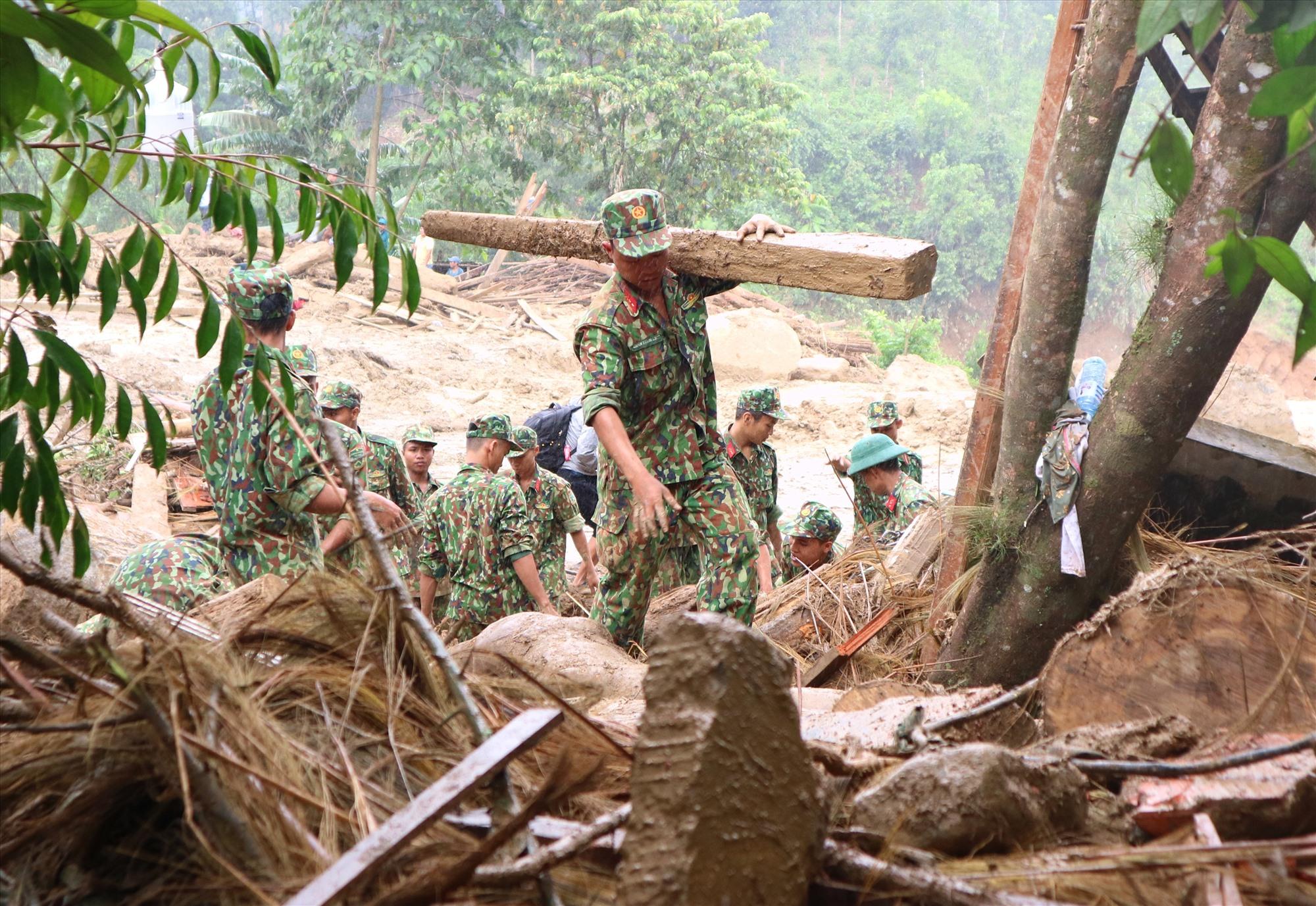 Một chiến sĩ vác khúc gỗ sườn nhà khỏi vị trí hiện trường tìm kiếm. Ảnh: P.V