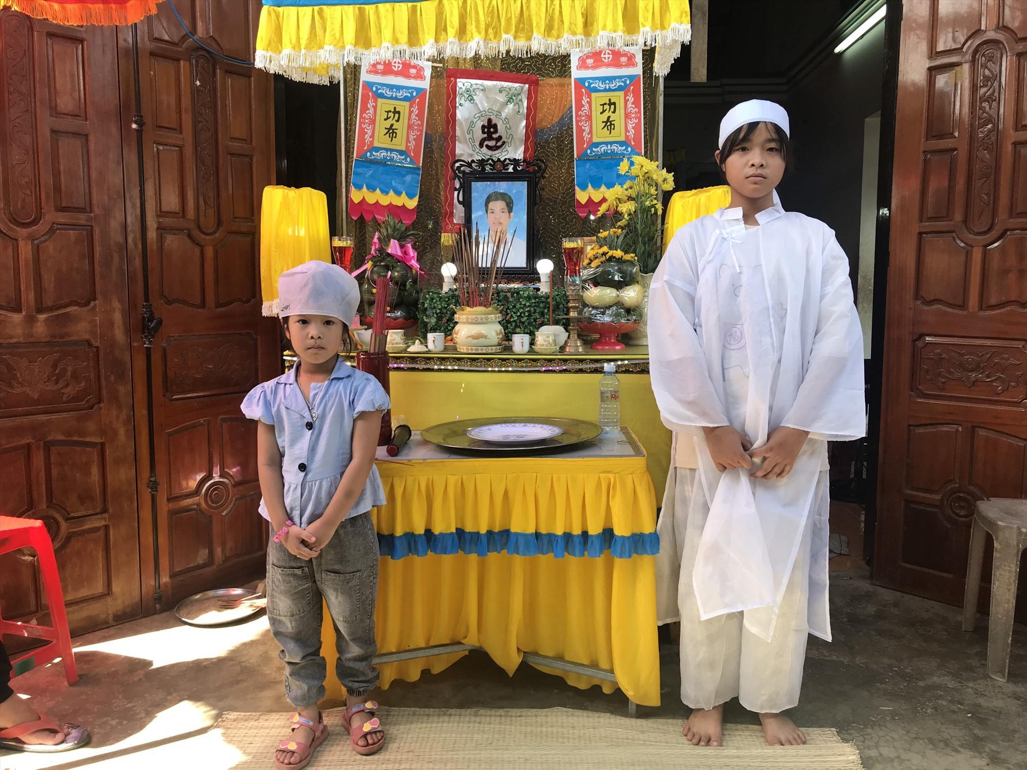 Hai cháu Nhân và Ngọc trước bàn thờ của người cha đang được lo hậu sự tại quê nhà. Ảnh: D.L