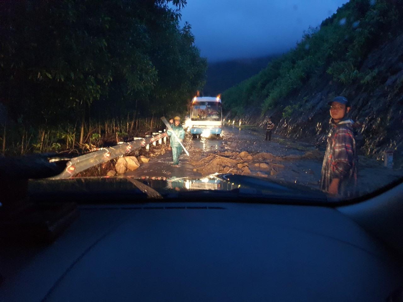 Lực lương chức năng khẩn trương thu dọn đất đá, đảm bảo giao thông. Ảnh MINH THÔNG