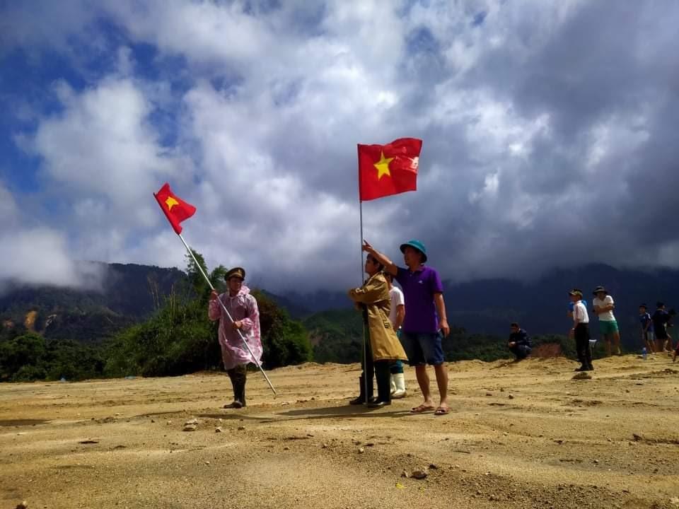 Người dân xã Phước Lộc dùng cờ Tổ quốc để đánh dấu địa điểm thả hàng cho trực thăng nhận diện. Ảnh: X.K