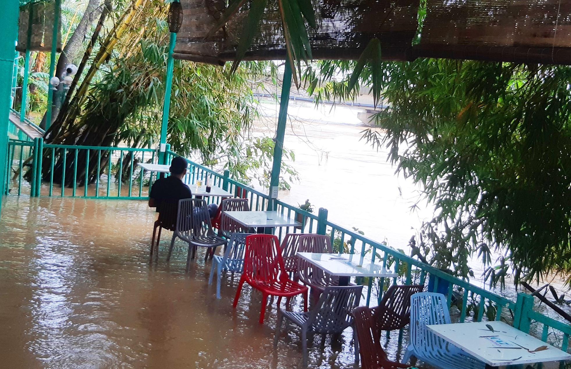 Nước lũ đã tràn lên một quán cà phê ven sông Vu Gia tại cầu Ái Nghĩa. Ảnh: HOÀNG LIÊN