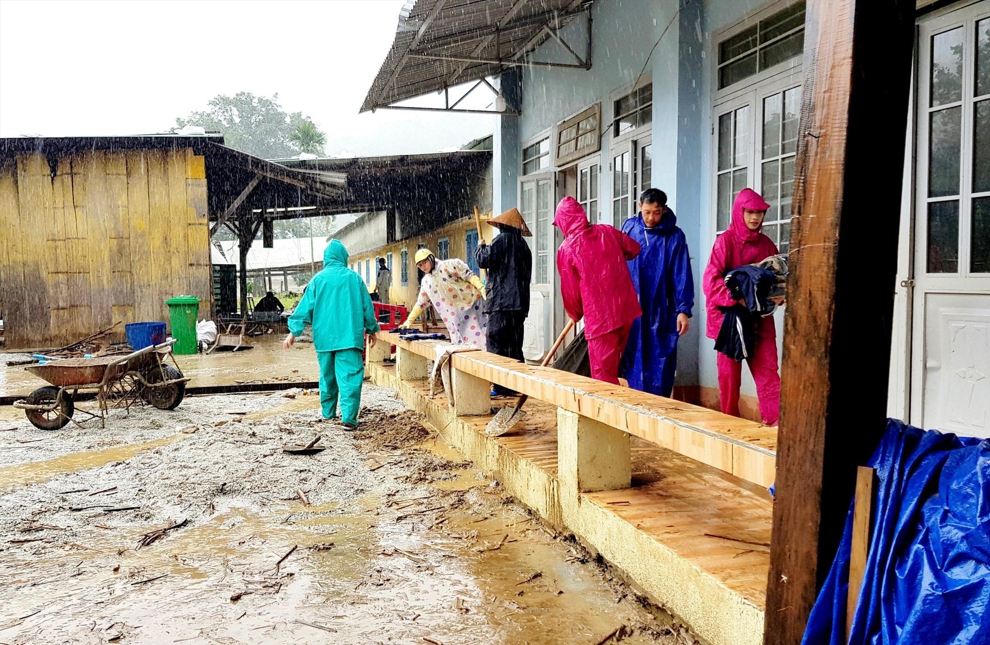Các thầy cô dầm mưa cùng tổng dọn vệ sinh trường lớp sau mưa lũ. Ảnh: PHI YẾN