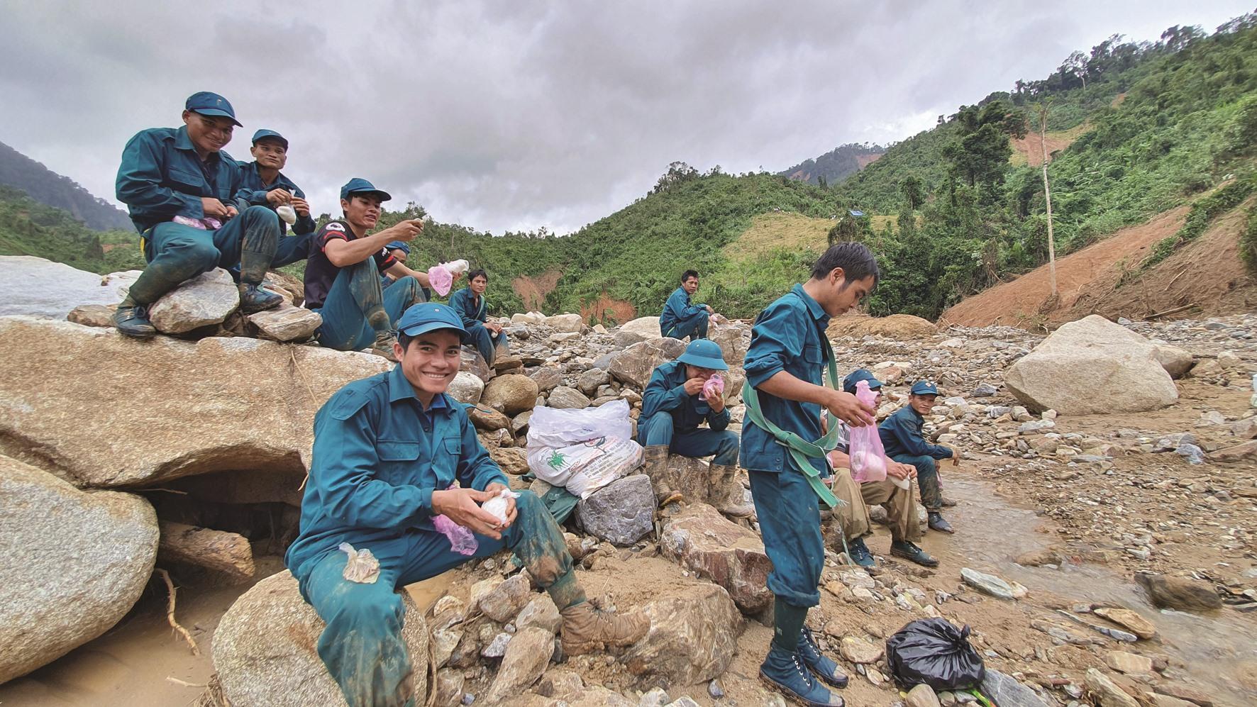 Bữa trưa của lực lượng dân quân xã Phước Kim gùi cõng hàng chi viện cho Phước Thành chỉ có nắm cơm và một ít cá khô, ngay bên lòng sông Trà Văn. Ảnh: G.C