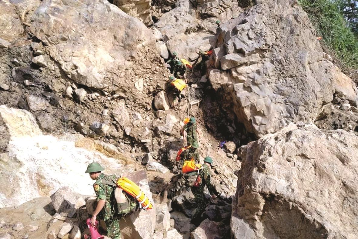 Cán bộ chiến sĩ căng dây, vượt qua đoạn núi đá lởm chởm trên đường vào Phước Lộc.