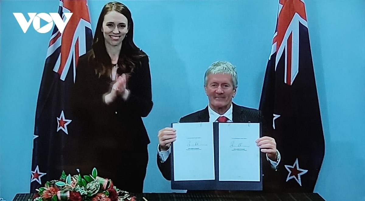 A New Zealand Minister pens the agreement in the presence of PM Jacinda Ardern