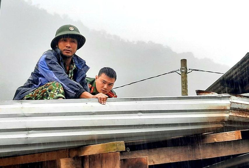 Trung úy Đoàn Thế Cẩm (bên trái) giúp người dân Phước Sơn lợp lại mái nhà sau bão. Ảnh: ALĂNG NGƯỚC