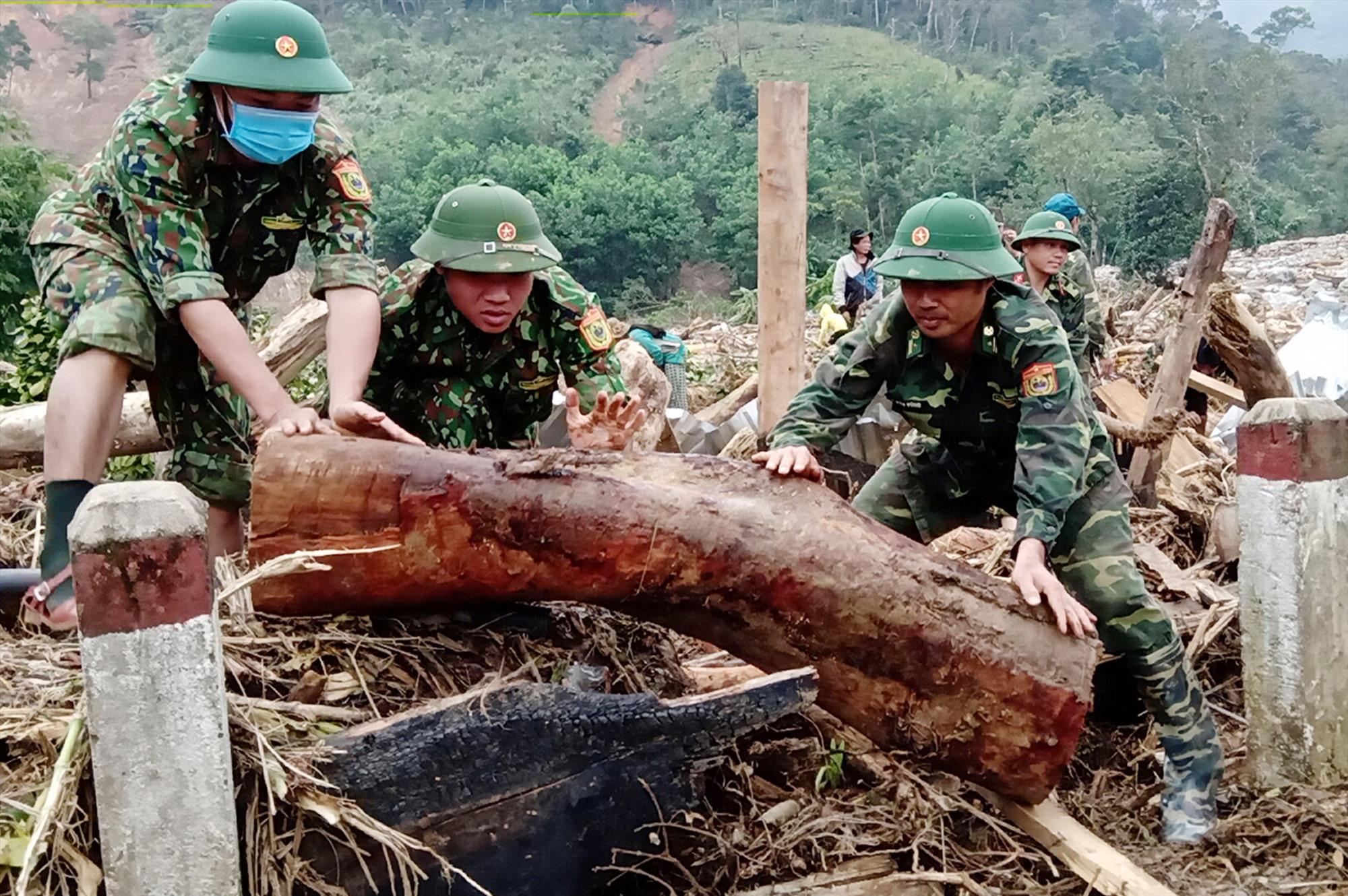 Thiếu tá Vông (bìa phải) tham gia tìm kiếm người mất tích tại hiện trường vụ sạt lở thôn 3 (xã Phước Lộc). Ảnh: H.T