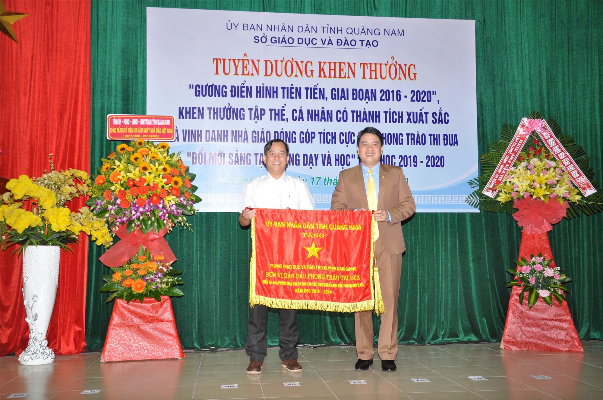 Phó Chủ tịch UBND tỉnh Trần Văn Tân tặng cờ thi đua xuất sắc của UBND tỉnh cho Phòng GD-ĐT Nam Giang. Ảnh: X.P