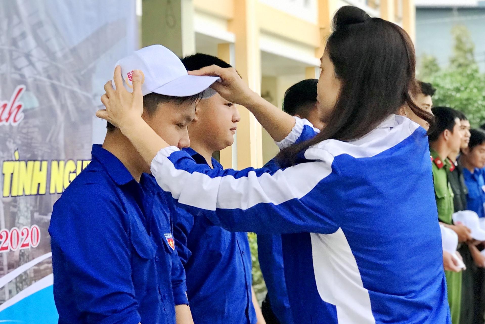 Bia thư Tỉnh đoàn Phạm Thị Thanh trao mũ cho thanh niên tình nguyện tham gia lễ xuất quân. Ảnh: VINH ANh
