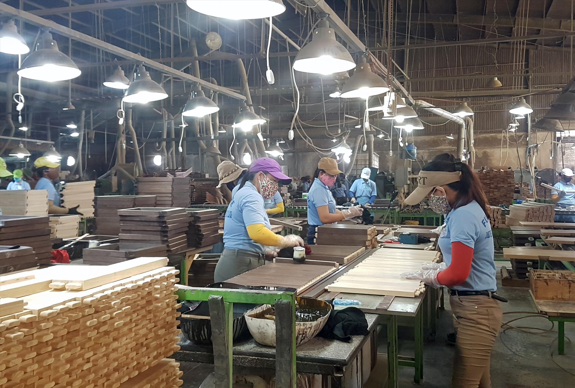 Công nhân lao động tại một công ty trong Khu công nghiệp Bắc Chu Lai sản xuất đảm bảo khoảng cách phòng chống dịch bệnh. Ảnh: D.LỆ
