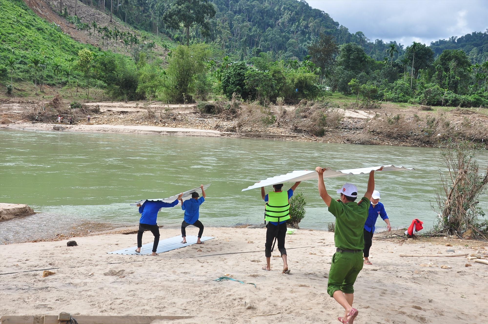 Vân chuyển các tấm tôn xuống bên sông. Ảnh: VINH ANH