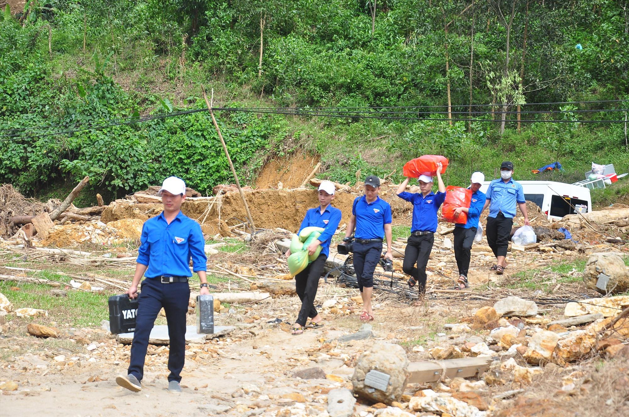 Từ quốc lộ 40B, đoàn tình nguyện cùng nhau vận chuyển đồ đạc, hàng hóa xuống bên sông để qua làng Tắk Rối. Ảnh: VINH ANH
