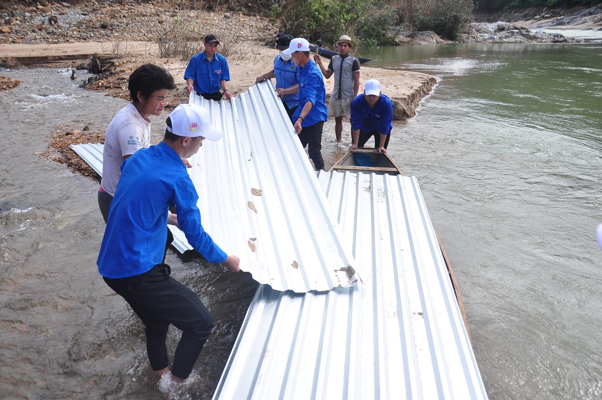 Xếp các tấm tôn lên thuyền nhỏ để vượt sông Tranh. Ảnh: VINH ANH
